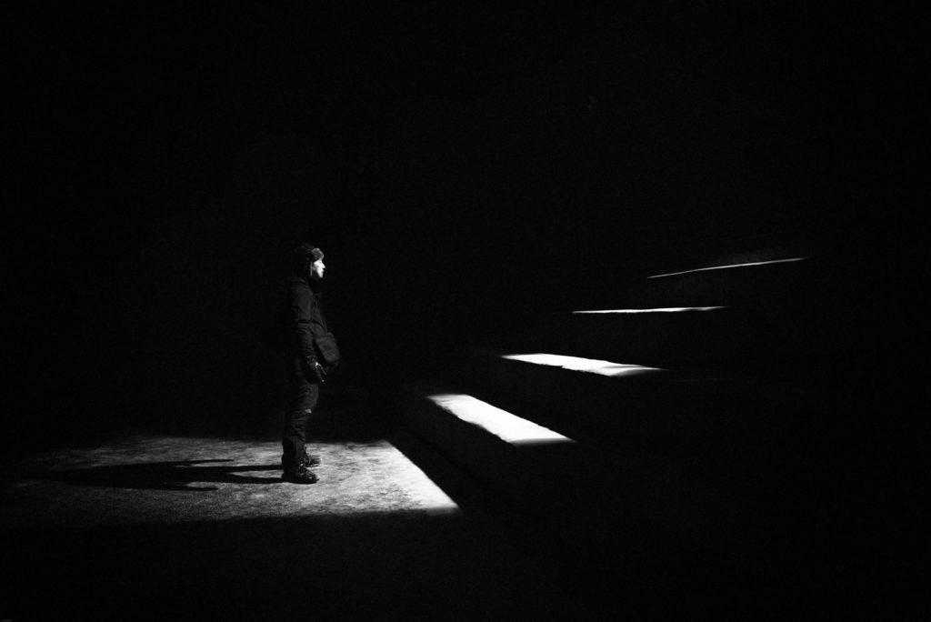Foto preto e branco de homem ao pé de uma escada